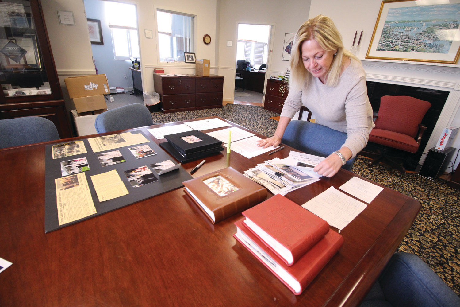 SO MANY ACHIEVEMENTS: Judith Earle, director of the Elizabeth Buffum Chace Center looks over photographs, newspaper clippings and letters documenting the history of the center founded 40 years ago.