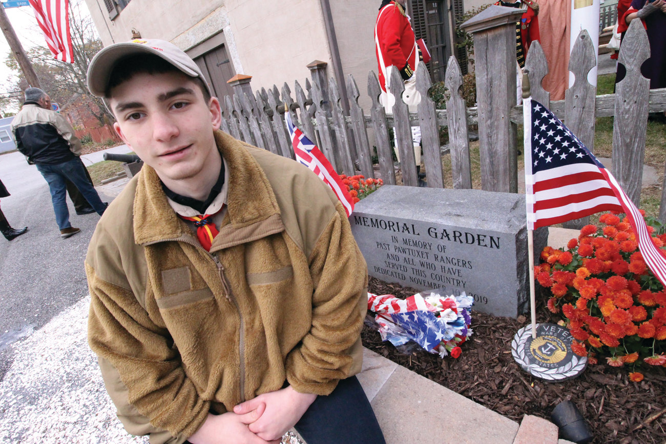 THE GARDEN HE HELPED BUILD: Nicholas Loffler is seen at the memorial that he and members of Providence Troop 76 built at the Pawtuxet Rangers Armory.
