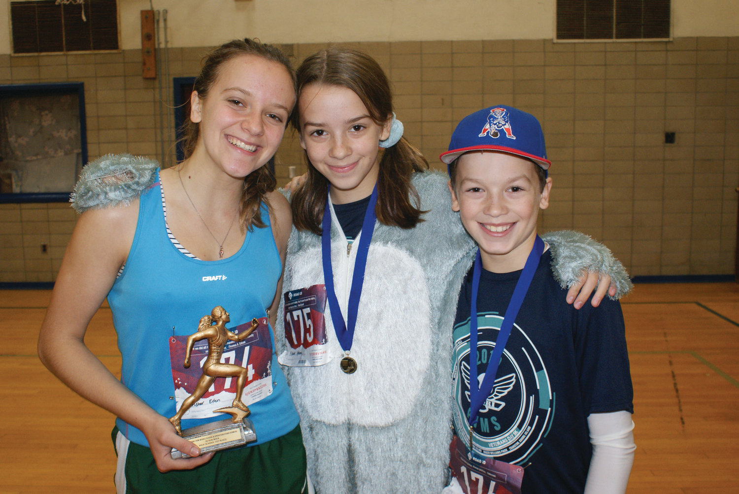 WINNING SMILE: Eden Fisher, a senior at Cranston High School East, won first place in girls high school category with a time of 21 minutes, 32 seconds. She celebrated with siblings Helena and Harrison.