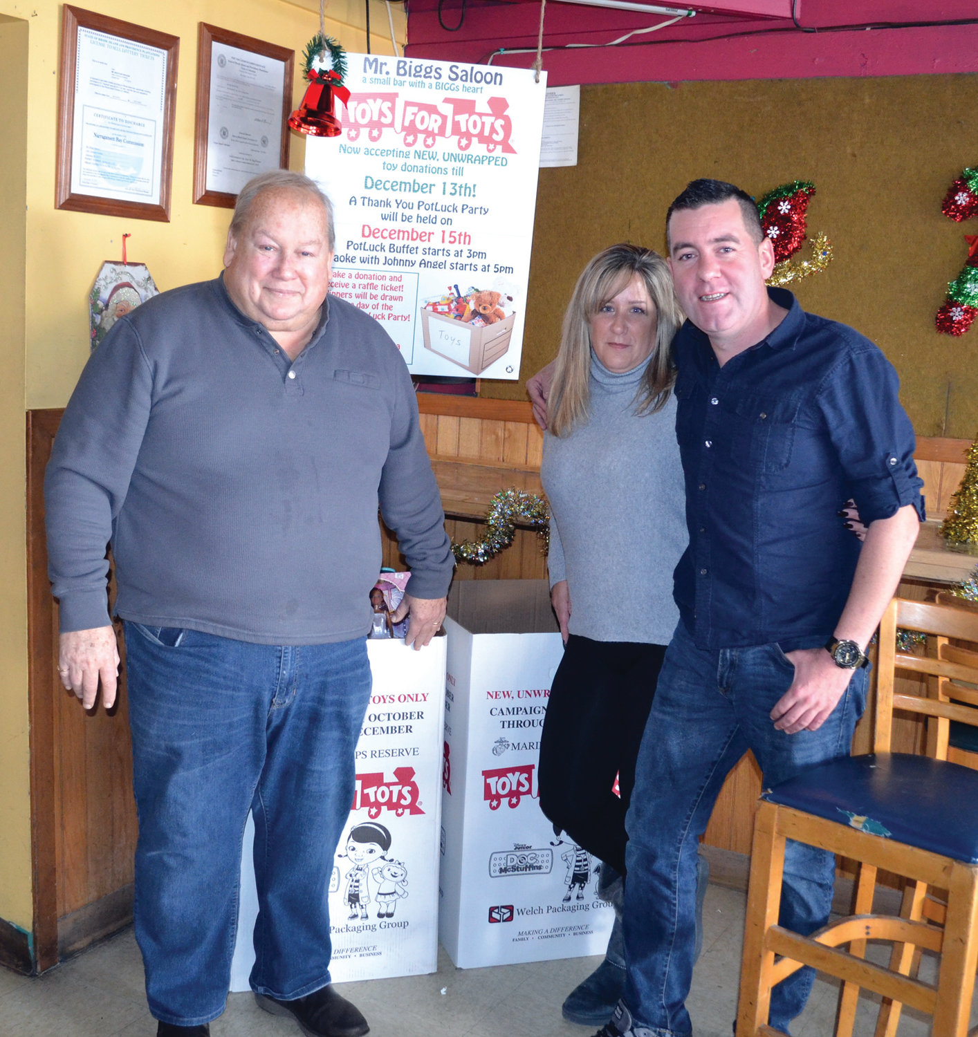 THE DRIVE IS ON: From left to right, Mr. Biggs Saloon owner Dennis Fried and bartenders Kristine Truppi and Eugene Gormley pose next to boxes they hope to fill with donations for Toys for Tots.