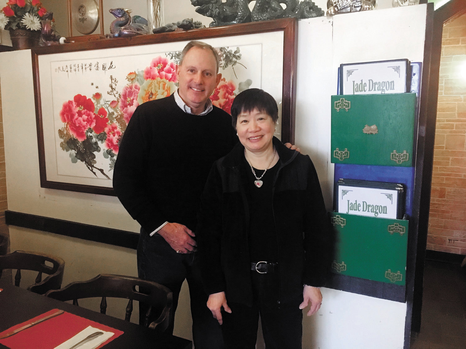 "RIGHT AT HOME: Judy Chin shares a moment with Ron Martin, a longtime friend and customer who has been dining at Jade Dragon since its opening nearly three decades ago. ""It's a neighborhood place,"" Chin said. ""People walk in here and they know everybody."""
