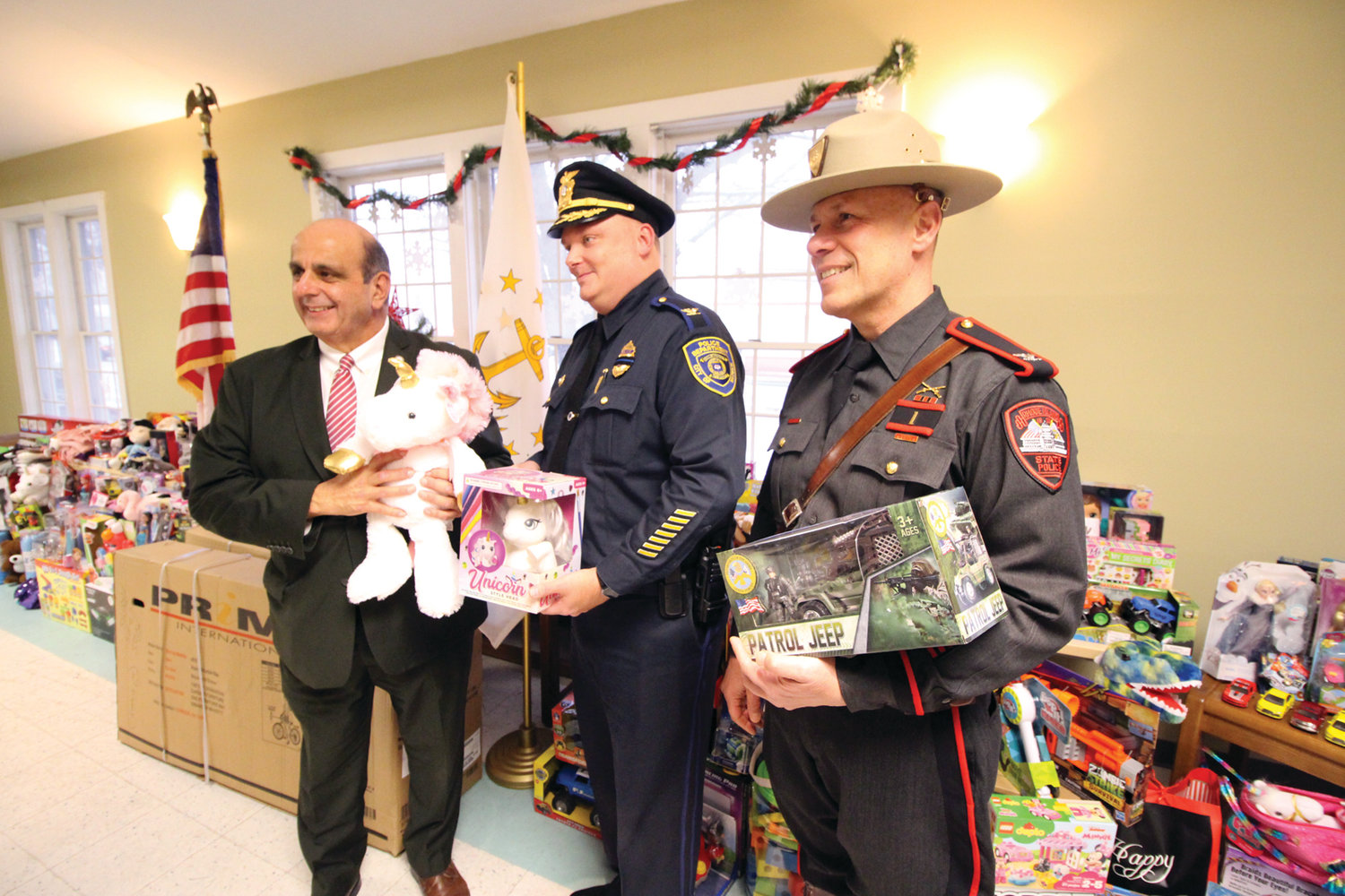 "NO TOYING AROUND: Mayor Joseph Solomon, Police Chief Col. Rich Rathbun and State Police Col. James Manni join for a photo at the ""Kids, Cops and Christmas"" event Tuesday at Buttonwoods Community Center."