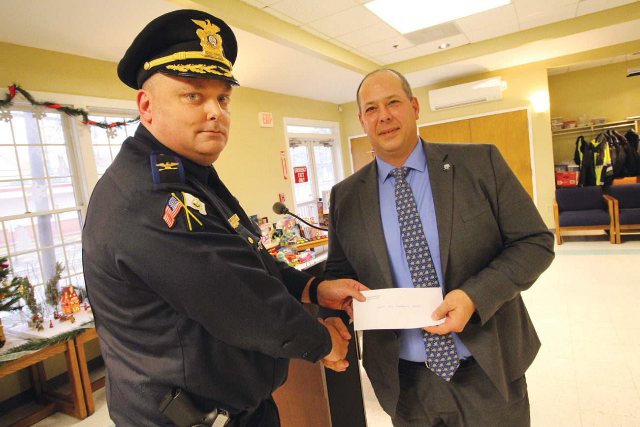 GREAT TIMING: Warwick Police Chief Col. Rick Rathbun presents a $250 check from the RI Police Chiefs Association to Westbay Community Action director Paul Salera. Salera said the money will help by Christmas gifts for a woman who now finds she'll be caring for her sister's children.