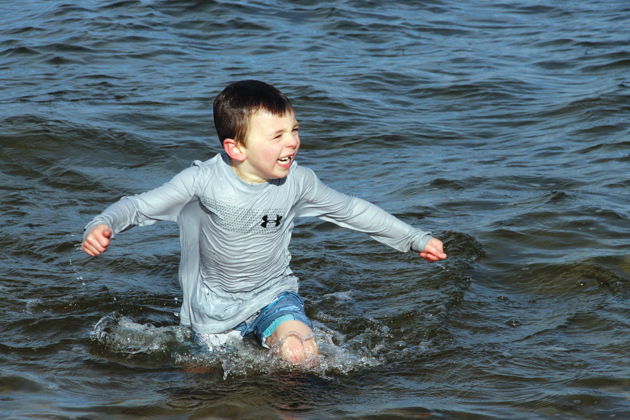 RUNNER AND PLUNGER: Luke McGowan, son of Ryan and Laurie McGowan of Laid-back Fitness that co-hosted the event for the benefit of Mentor RI, emerges from bay waters.