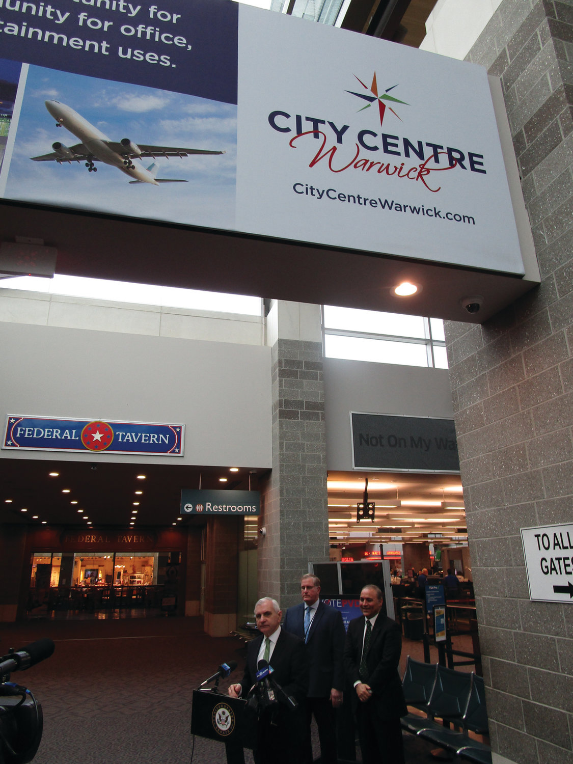 LOCAL DESTINATION: Next to the airport's security checkpoint and beneath a sign advertising City Centre Warwick, U.S. Sen. Jack Reed, TSA Federal Security Director Daniel Burche and Rhode Island Airport Corp. President and CEO Iftikhar Ahmad addressed members of the media on Friday.
