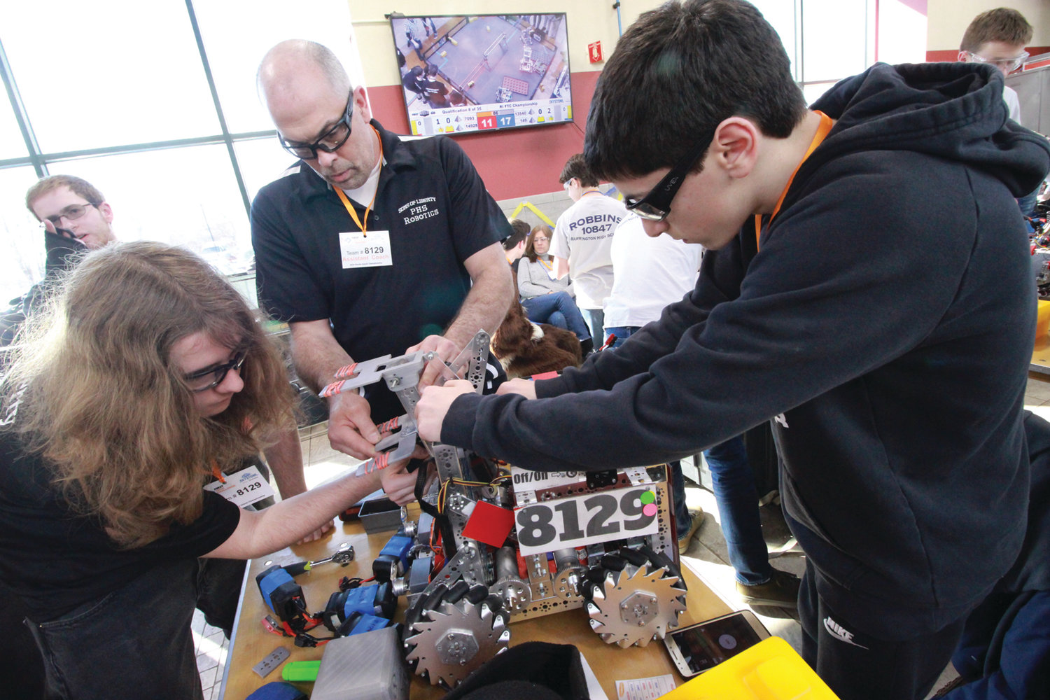 ADJUSTMENTS: Ryan Sanita, coach Larry West and John Miller make adjustments to the Pilgrim robot between rounds in Saturday's competition.
