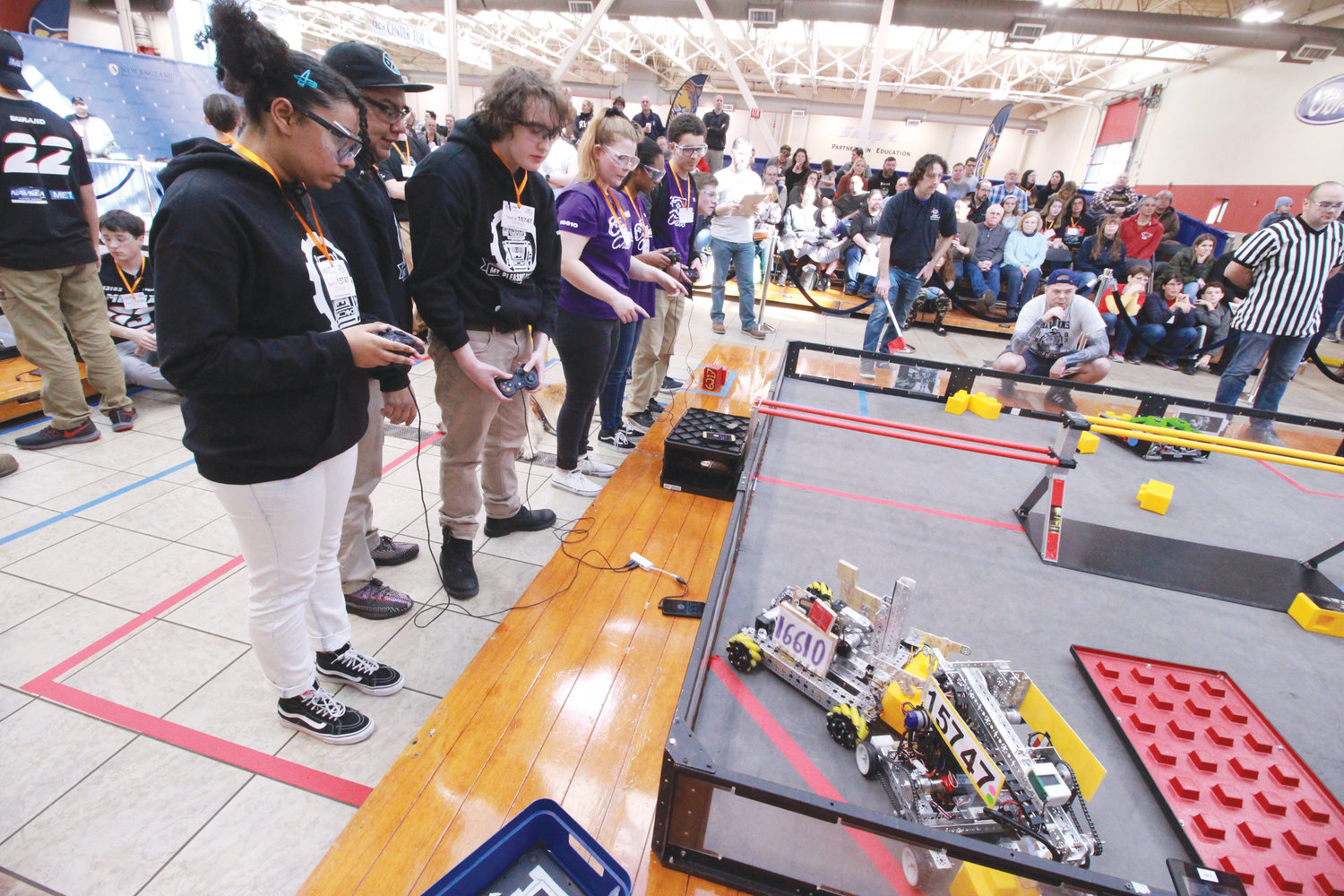 BATTLE OF THE BOTS: Teams face off in the opening round of the FIRST Tech Challenge held Saturday the NEIT automotive center.