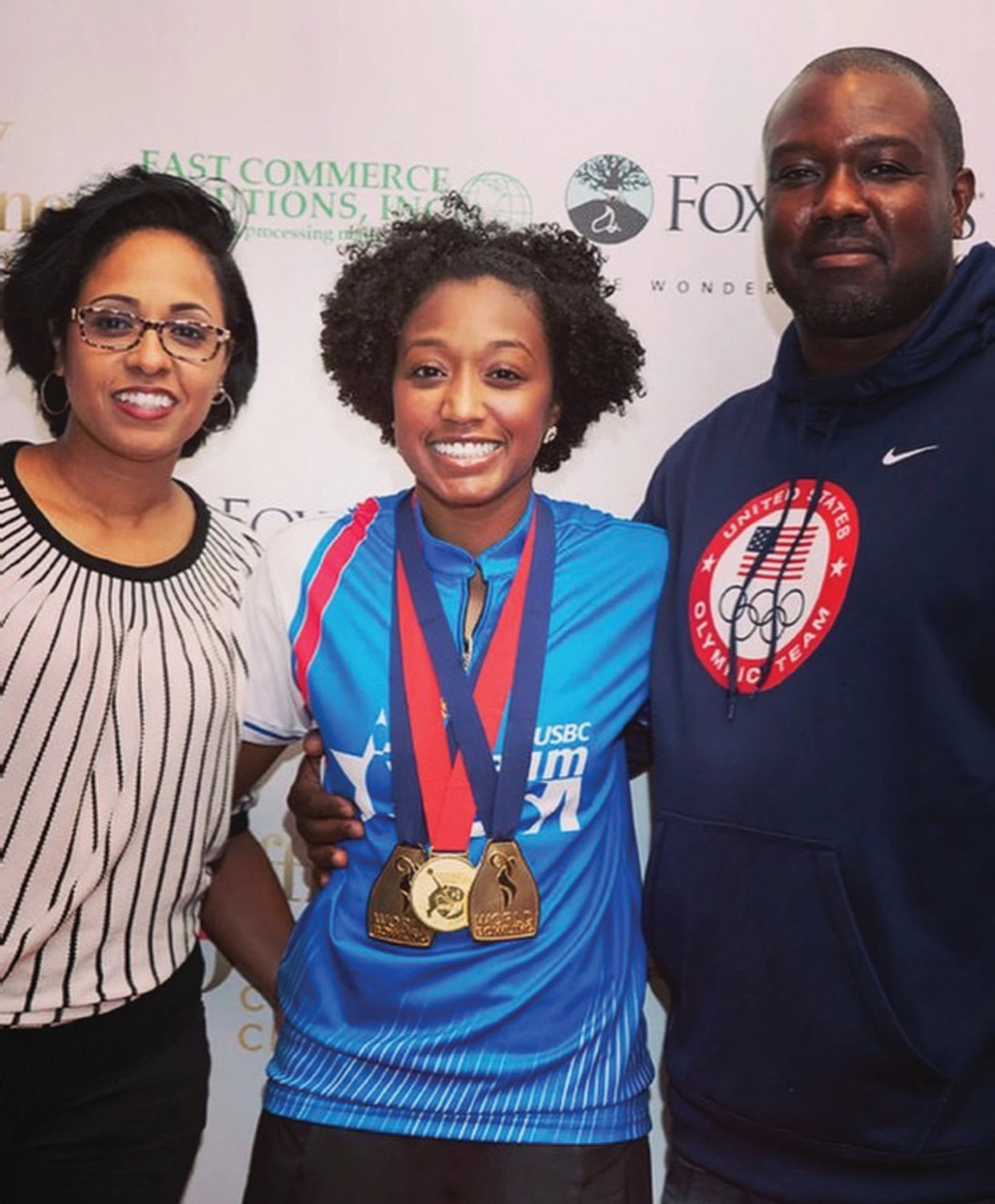 GOING FOR GOLD: Gazmine Mason shows off her gold medals while sharing a moment with her mother, Danielle Daley-Mason, and father, George Mason.