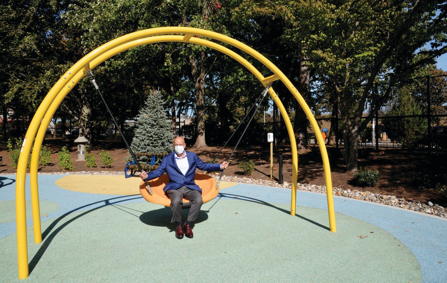 TAKING A SWING: Tom Rezendes, senior vice president at Pariseault Builders, tries out the swing at the revamped playground at Hasbro Children's Hospital during a recent visit. The Cranston-based led the construction effort of the project.