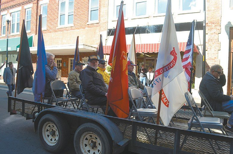 Surrounded by flags representing each branch of the service, veterans make their way down Main Street toward the Person County History Museum