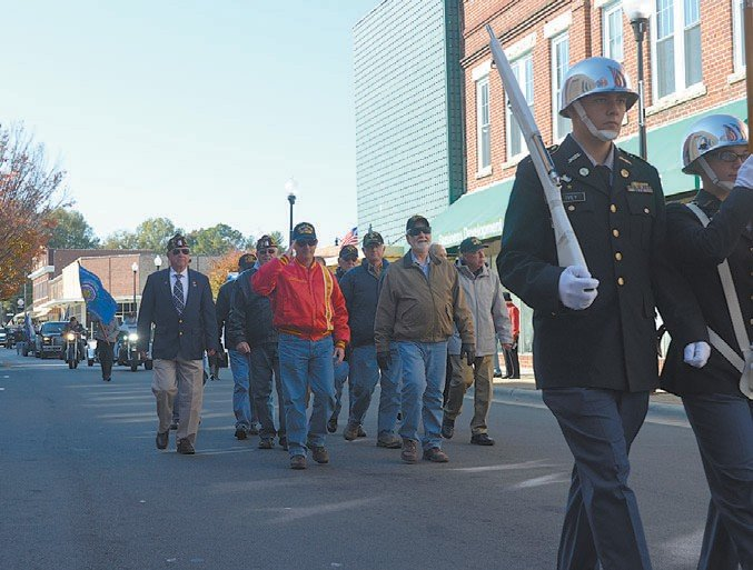 U.S. military veterans parade down Main Street in Roxboro on Saturday morning, led by a JROTC honor guard.