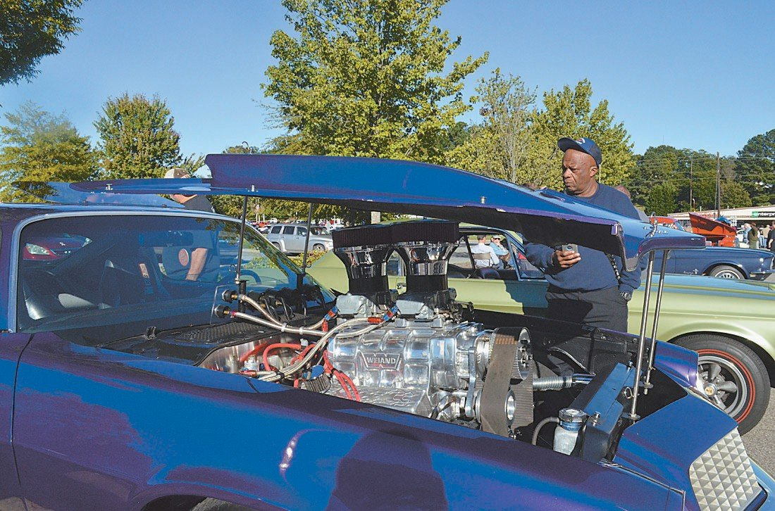 Roxboro Fire Chief Kenneth Torain inspects the inner workings of a car on display at Saturday's Cruise in.