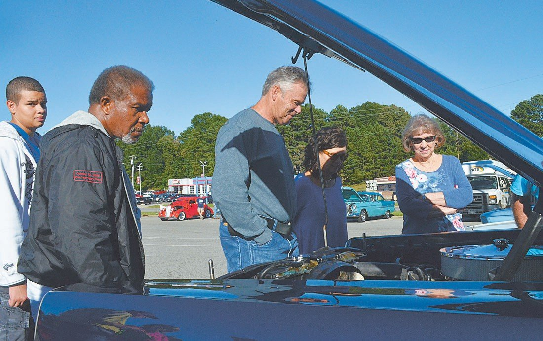 Randy Clements, center, takes a look under the hood of one of the classic cars on display at Saturday's Cruise-In.