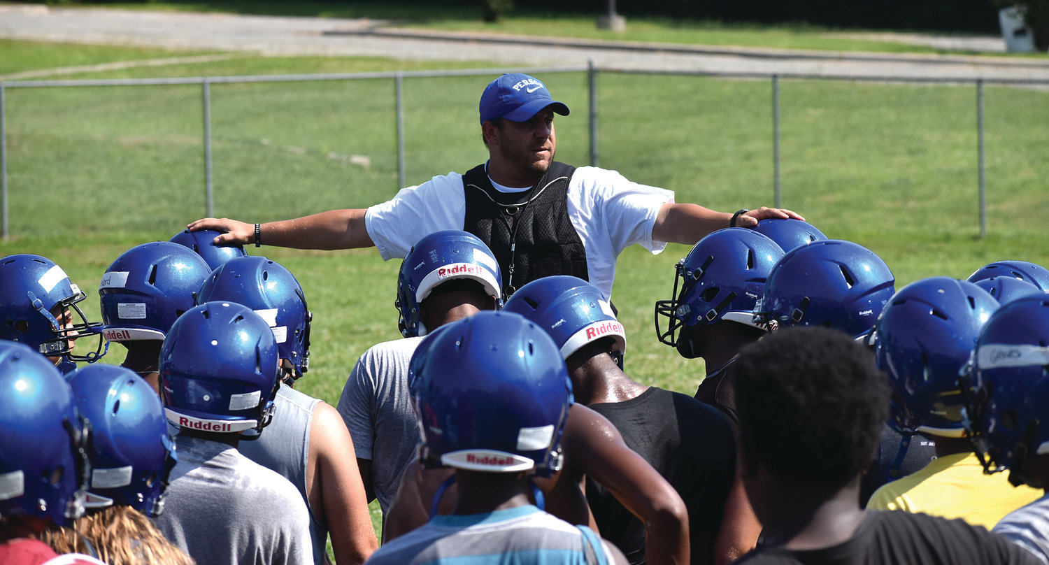 Dave Kleine, shown here addressing his team during a summer workout, resigned as Person's head football coach Thursday.