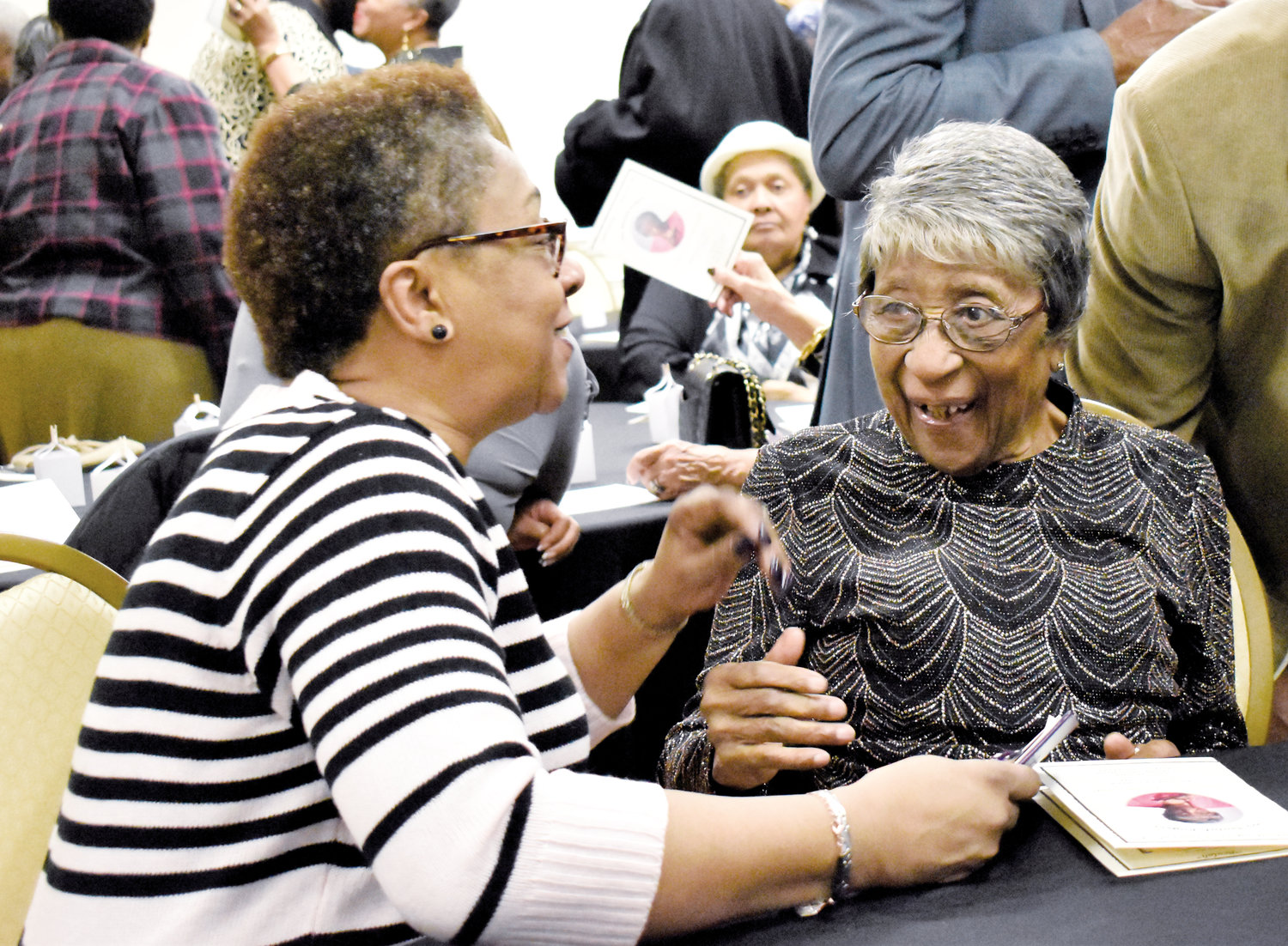 Beulah Rogers, right, visits with her neice Phyllis Lattie during a celebration of Rogers' 100th birthday.