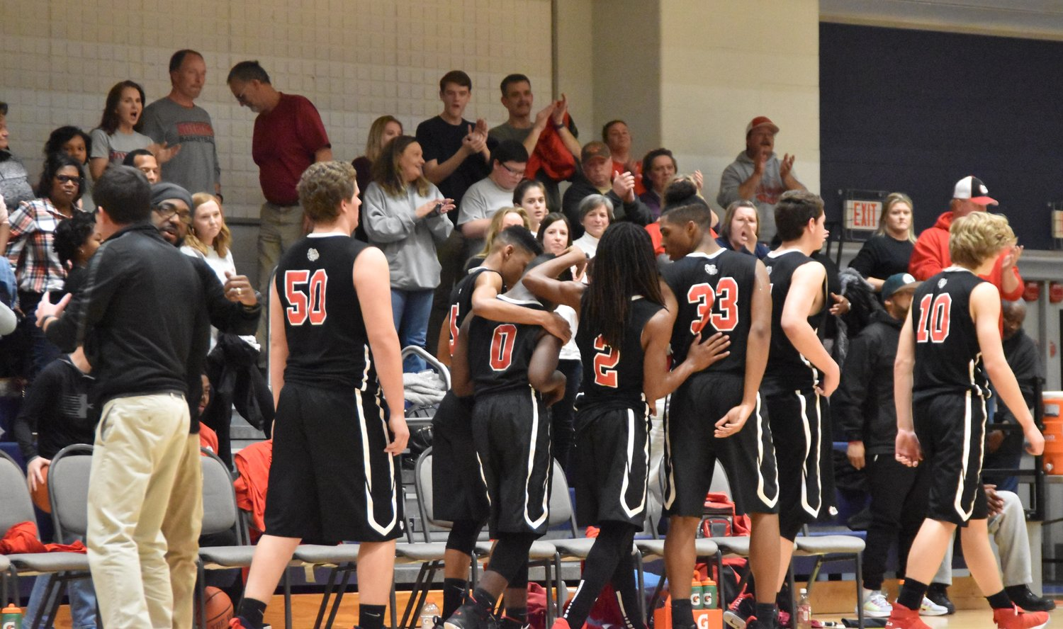 Players on the Roxboro Community School boys' basketball team console each other while getting cheers from their supporters following their 71-57 loss at Henderson Collegiate in the fourth round of the 1A state playoffs Tuesday. It was the deepest playoff run in the program's history.