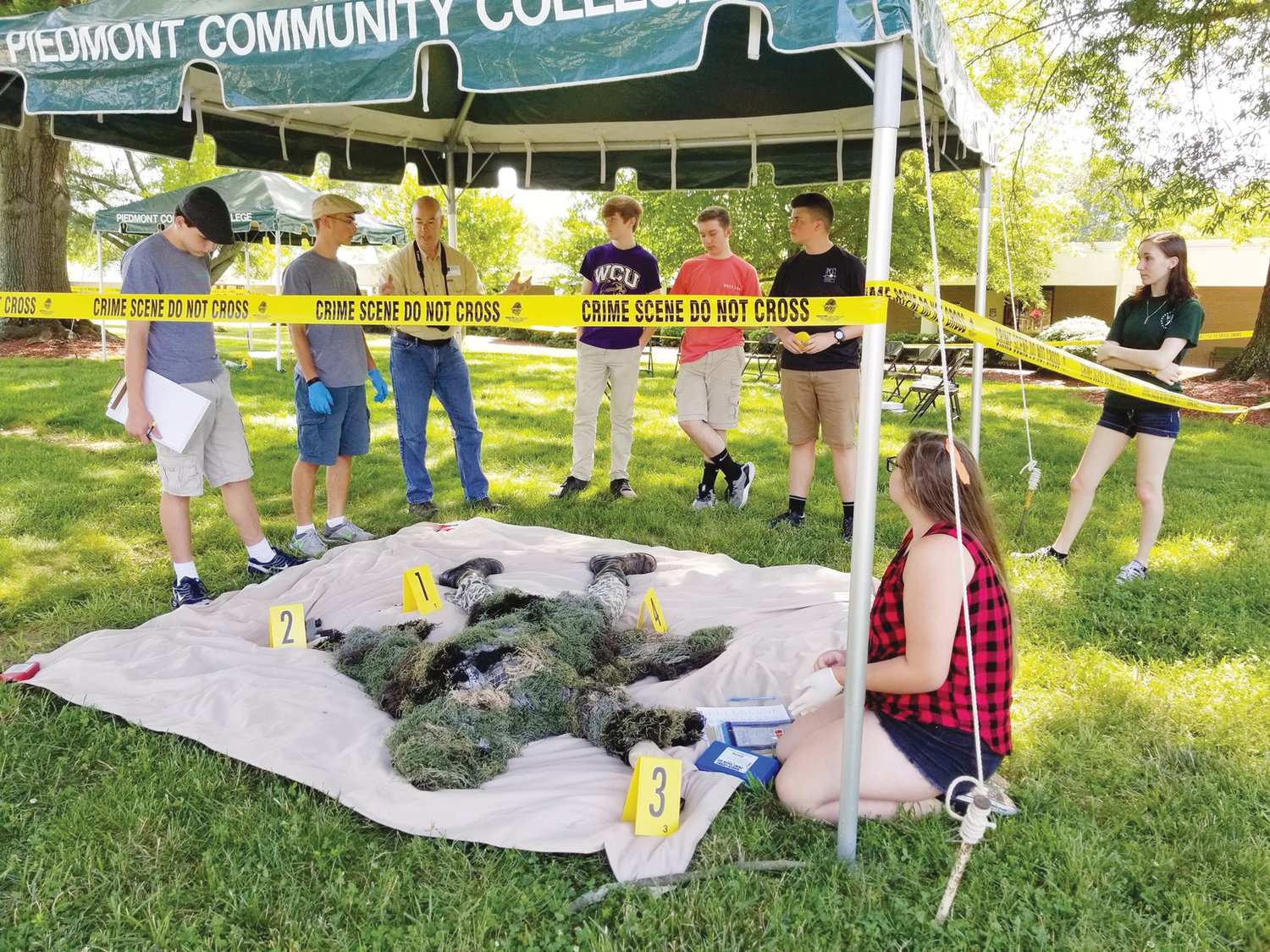 Students take notes at a mock crime scene as part of a PCC Criminal Justice summer camp last year.