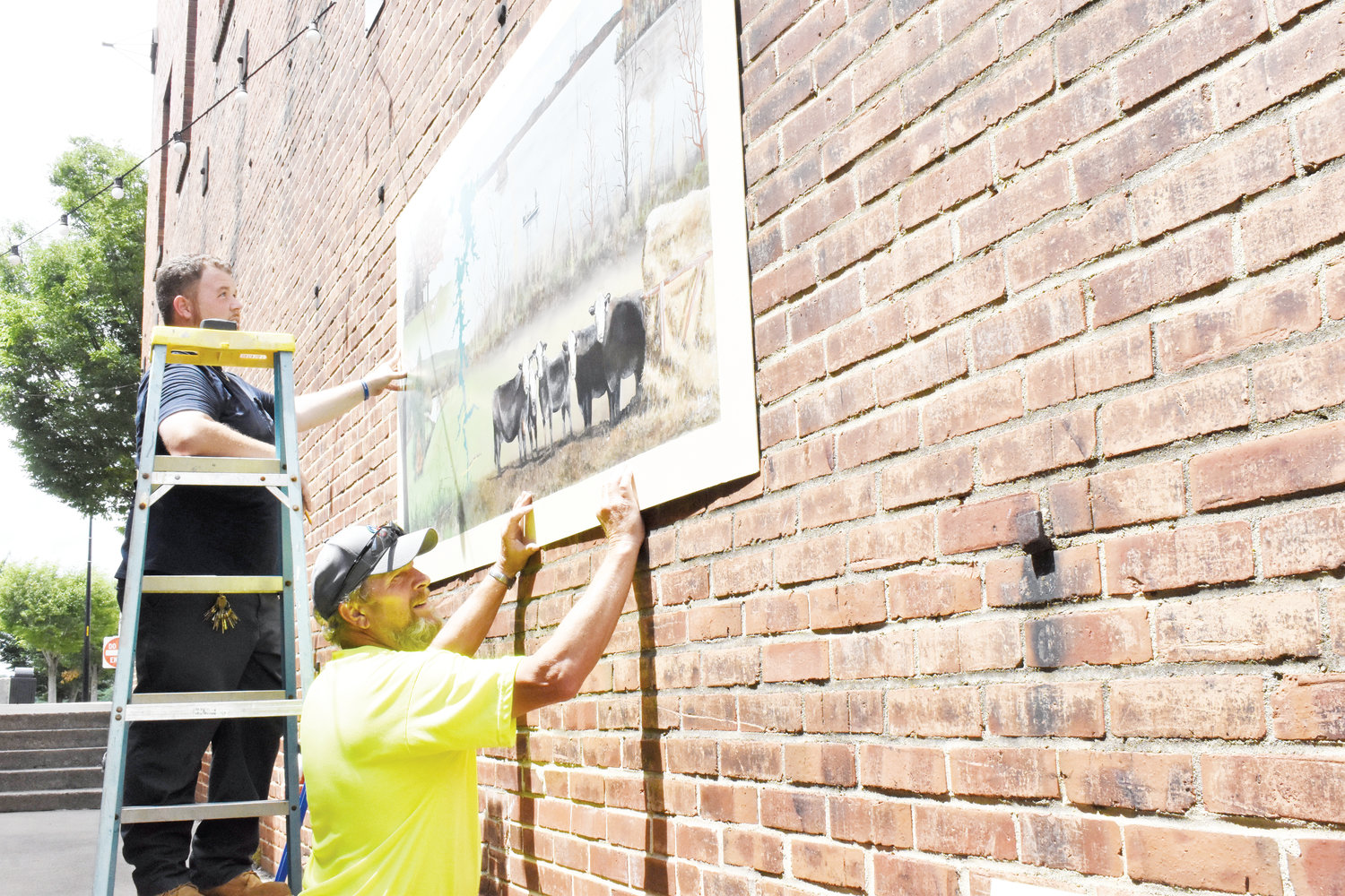 Phillip Fish, left, and Mike Clayton install one of five pieces of art that now adorn the pedestrian alley across from the Person County Courthouse. Three more pieces will be put up this summer.