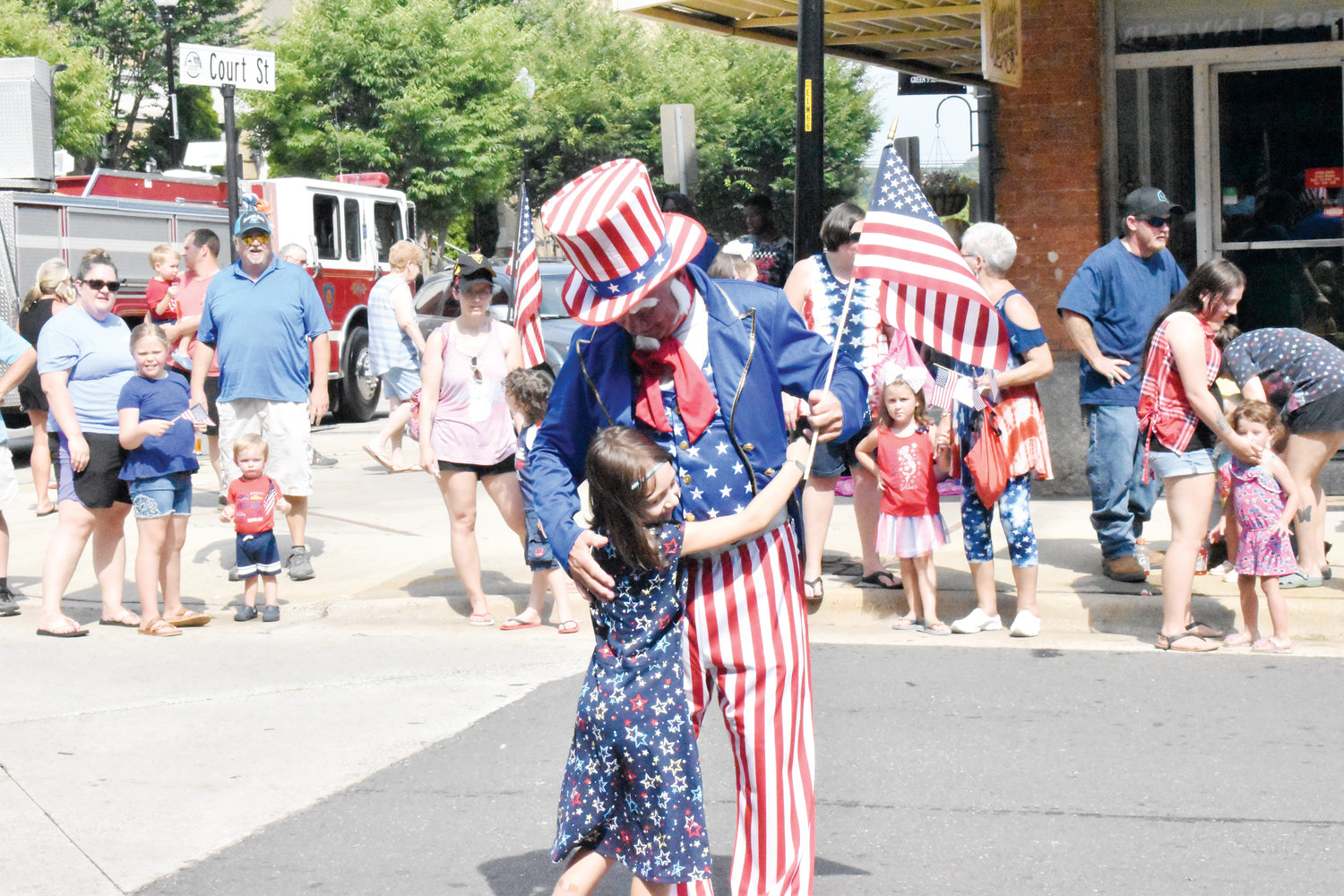 Aria Bridges, 7, ran out into the Roxboro Independence Day parade to give Uncle Sam a hug as he walked down Main Street.