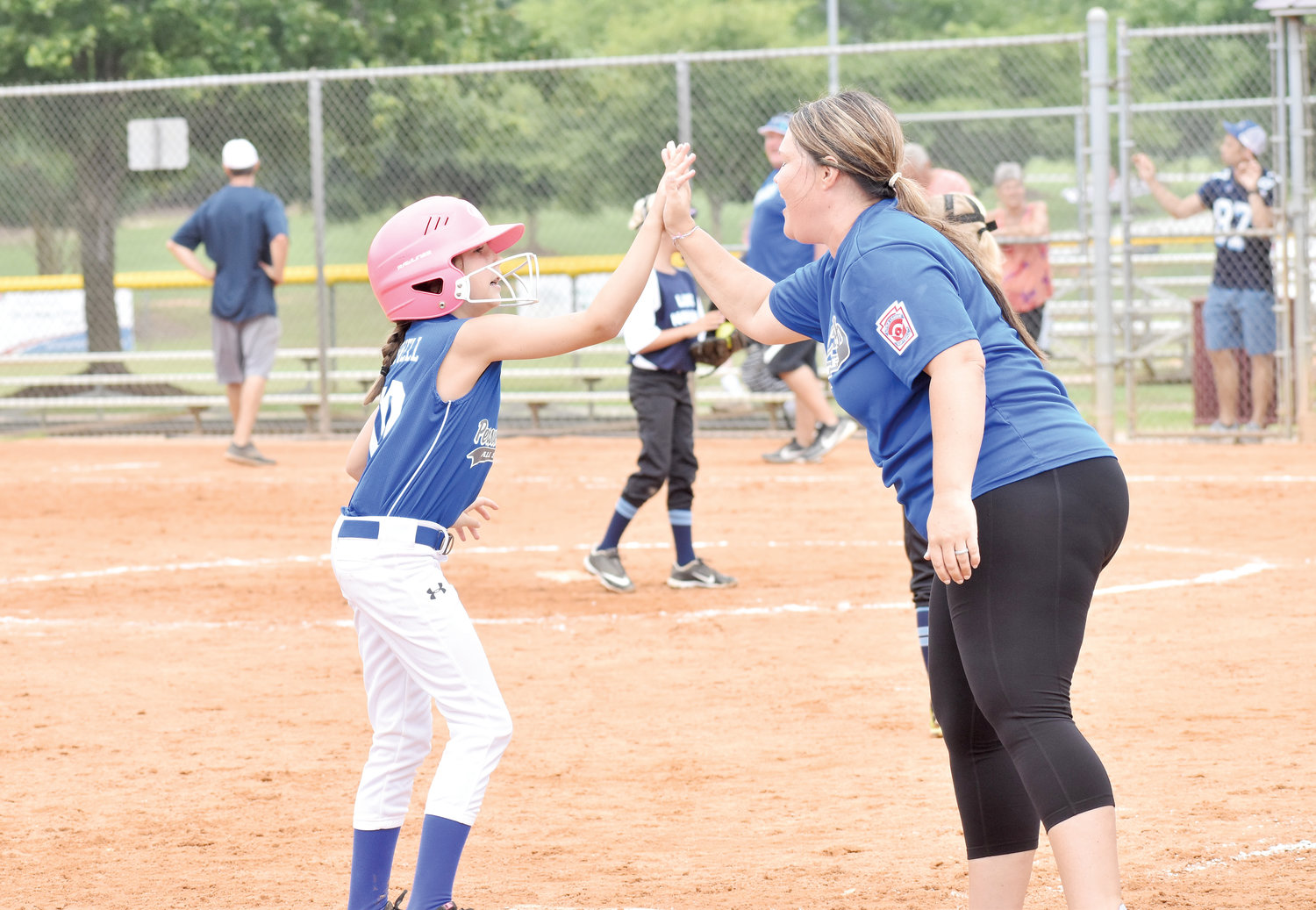 Kelly Snow | The Courier-Times.Person County Little League 8U All-Star Lexi Powell gets a big high-five after hitting a triple in last Saturday's game against Lake Norman.