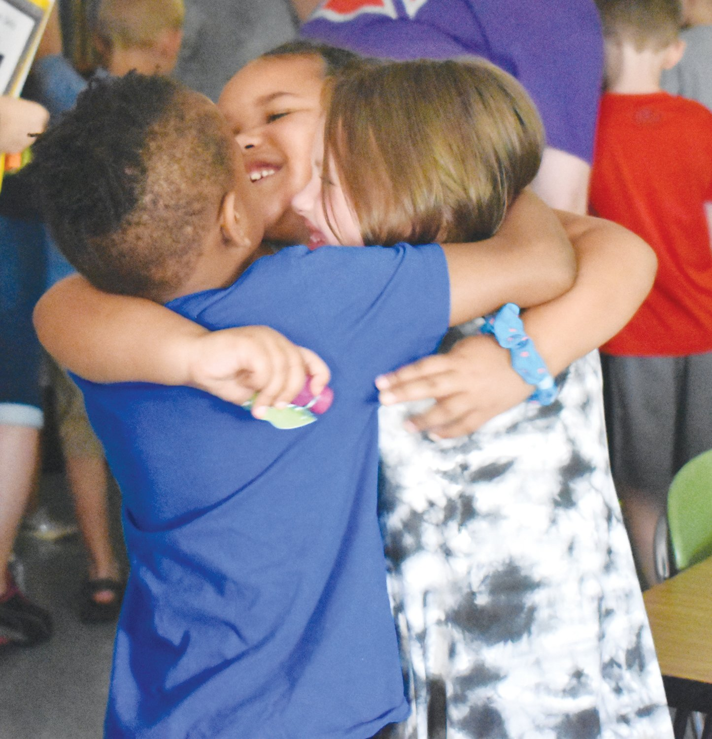 Bethel Hill Charter School students, from left, Gabriel Stokes, Juliann Torian and Khloe Tingen-Hicks share a hug after learning what first grade will be like.
