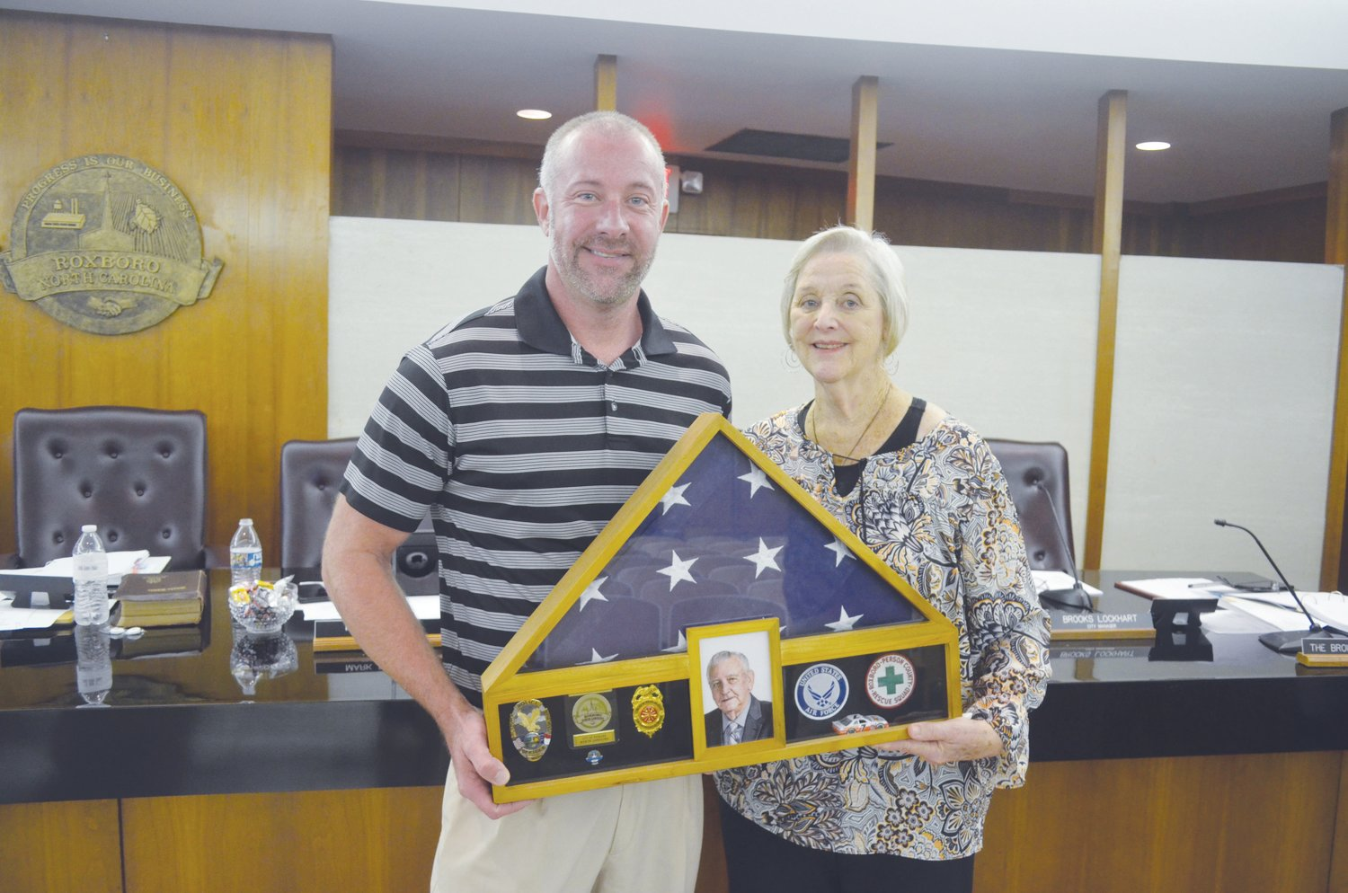 Charlotte Humphries Stigall, right, and Michael Stigall hold the shadowbox honoring their husband and father, Sandy Stigall, presented to them by the Roxboro City Council.