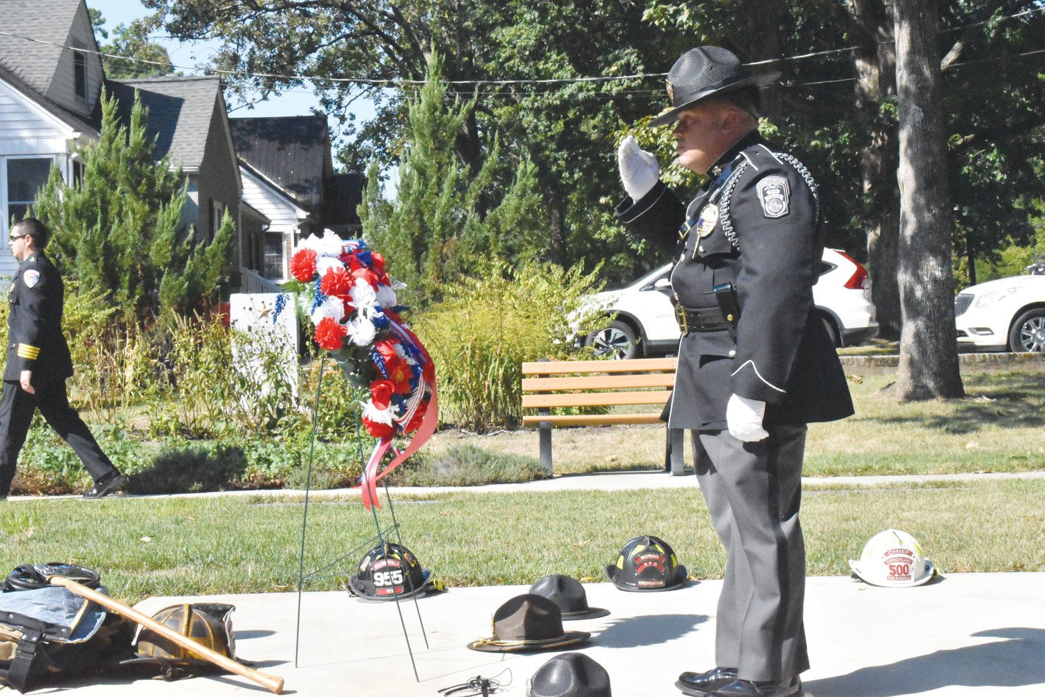 Roxboro Police Lt. Dan Walker salutes after laying a police cap on the ground in front of a wreath during Saturday's Patriot's Day observance.