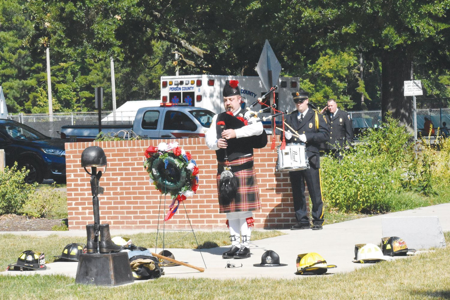 Roxboro Fire Department's Robert Miller plays the bagpipes at the close of Saturday's Patriots Day observance. Miller was escorted into the park by firefighter and snare drummer Blake Whitt.