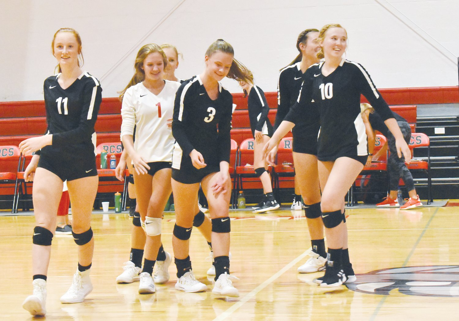 RCS volleyball players celebrate a five-set win over East Wake Academy Monday night in Roxboro.