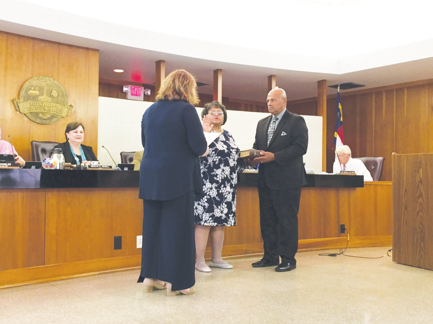Person County Clerk of Court Deborah Barker leads new City Council member Cynthia Petty, center, through the oath of office while  her husband Steven Petty holds the Bible.