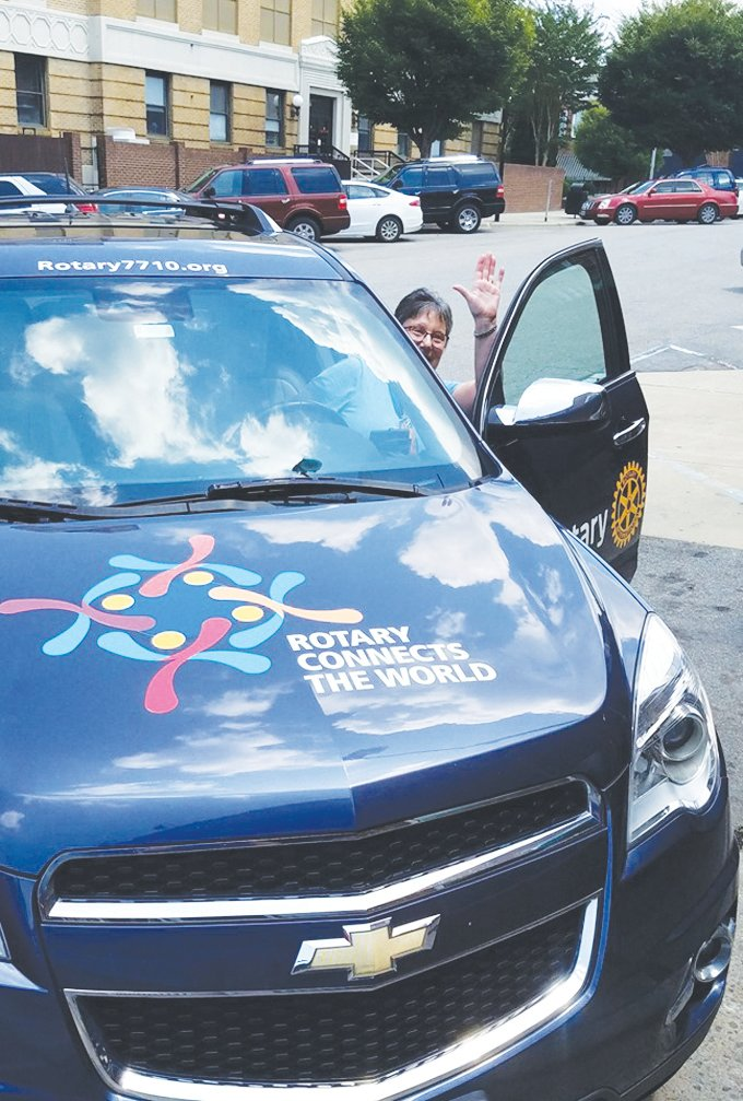 Rotary District Governor Marie Howard waves as she arrives in Roxboro to meet Roxboro Rotarians during her official visit to the club. Her Rotary One car has drawn raves as she has traveled to events around the district.