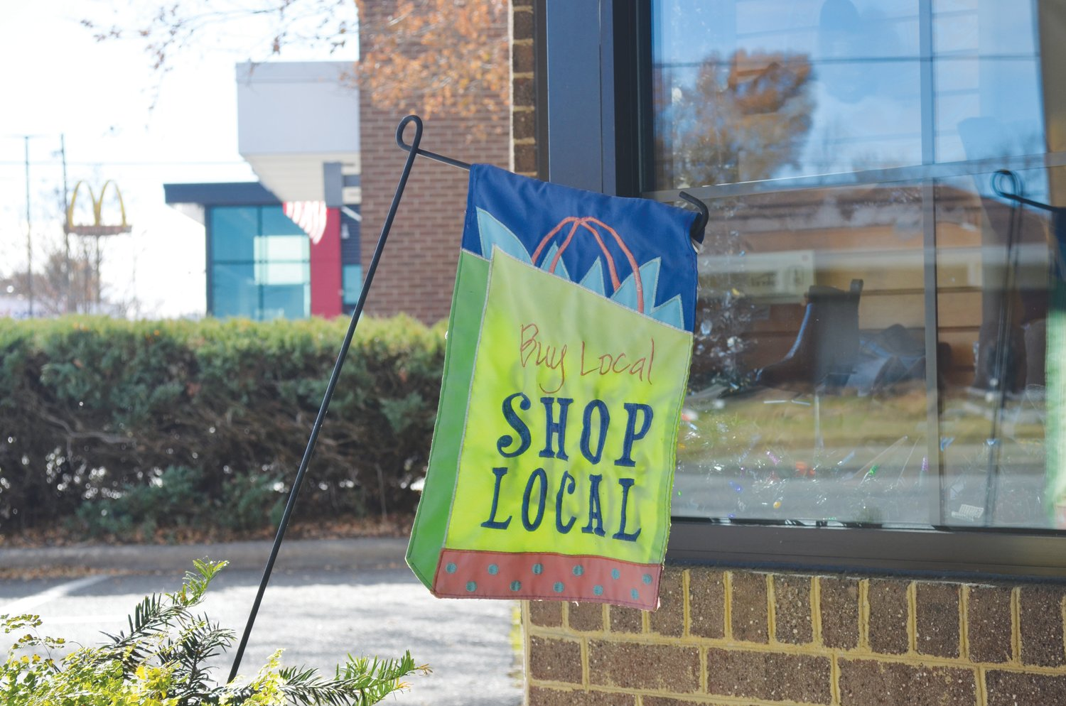 A flag at The Bootery Ltd. encourages shoppers to support local businesses.