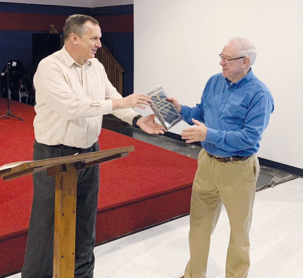 Dr. John Carpenter, left, presents Joe Scruggs a plaque to mark his service as an elder and evangelist.