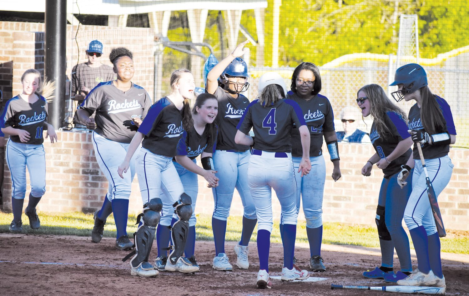 Person softball player Taylor Sullivan (4) is greeted by teammates after belting a solo homer during a Lady Rockets game last year against Halifax County (Va.). Sullivan is one of 11 returners for a Person team poised to make another run at the state playoffs.