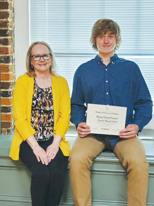 Bryson Pleasant, right, won the Good Citizen Award for Roxboro Community School. DAR Good CItizen Committee chairwoman Pamela Wood presented him with a certificate noting his honor.