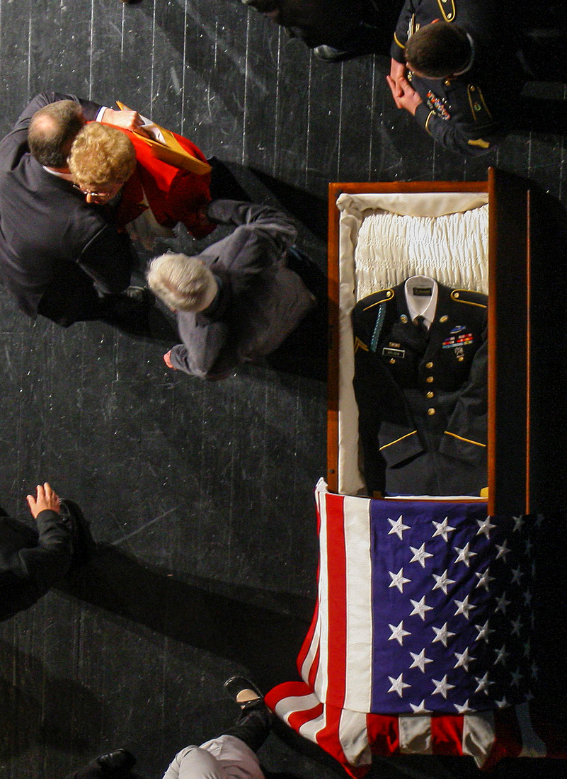 Family and friends gather around Geraldean Johnson, in red, widow of U.S. Army Cpl. C.G. Bolden, beside a casket with his recovered remains before the start of a memorial service for the Korean War soldier Saturday in Clinton.