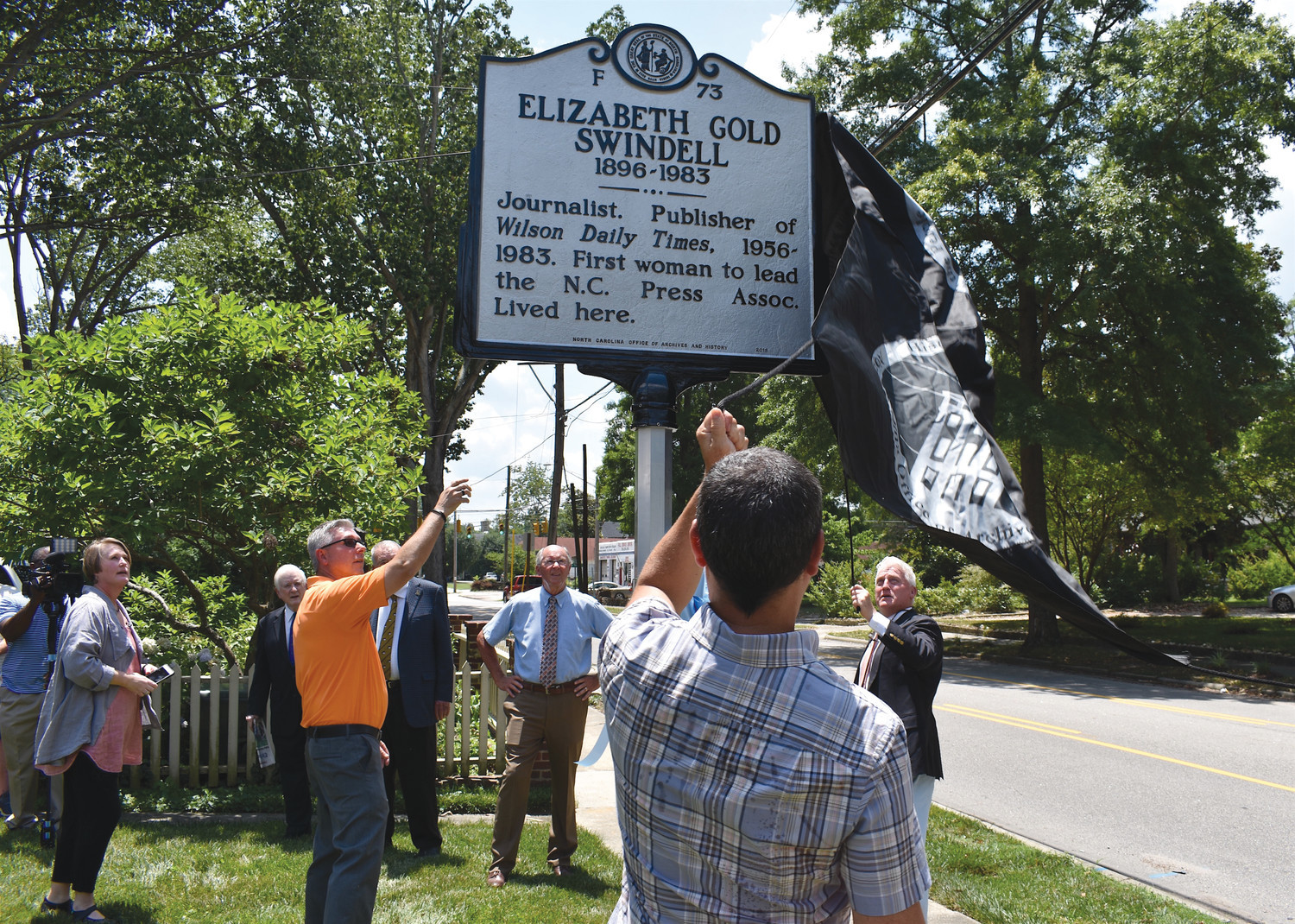 Times president and publisher Keven Zepezauer, left, and CEO and chairman Morgan Dickerman unveil a state historical marker honoring Elizabeth Gold Swindell on Saturday. Swindell earned statewide and national recognition for her work while serving as The Wilson Times' owner and publisher. (Photo by Corey Friedman/The Wilson Times)