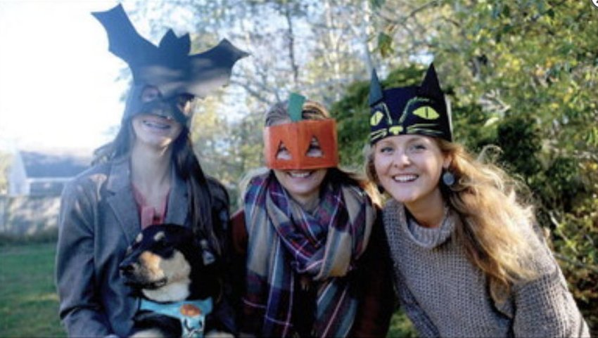 Cecilia, Maura, and Emily Wendelken with their dog Matilda, show off their cardboard masks and crowns.
