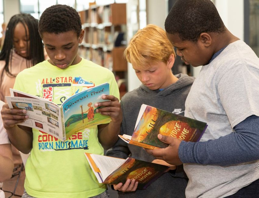 From left, Akeel Walker, Tyler Miller and Dakara Turner with Padma Venkatraman's books in the Cyrus Peirce School library this week. Venkatraman will visit the school to speak with students Tuesday.