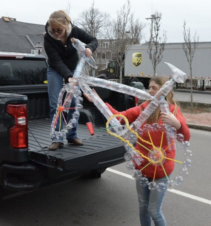 Phaedra Plank, on truck, and Tori Dixon unload the plastic bicycle sculpture created by the Nantucket High School art and environmental clubs.