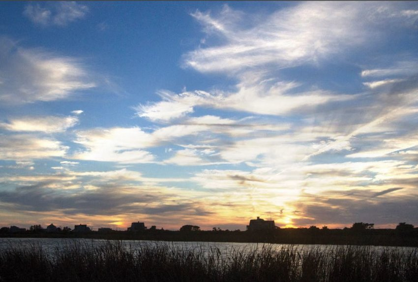 The sun sets over Miacomet Pond. The Land Bank has endorsed a proposal to dredge nearly two feet of nutrient-heavy sediment from the bottom of the pond to improve water quality and public health. Any work would probably not happen for at least a year.