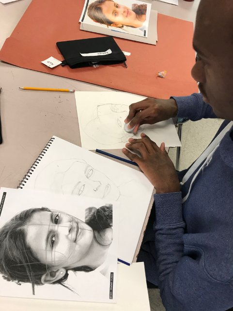 Rushawn Leamy works on his portrait of a Syrian girl as part of the Memory Project in Merrill Mason's high-school art class.