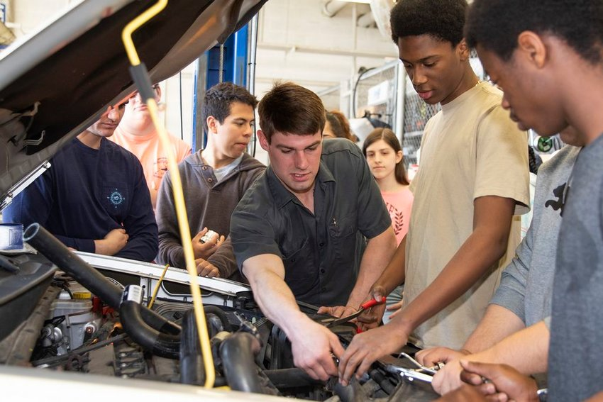 Nantucket High School automotive teacher Derek Mulson, left, works under the hood of a car with students Tuesday.