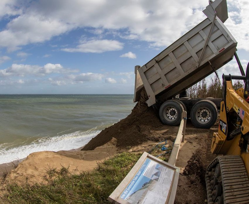 Sand is dumped over the side of the Sconset Bluff to replenish an erosion-control project on the beach below.