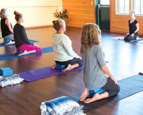 Dharma Yoga instructor Sheri Perelman, top right, leads a Hatha yoga class in the Hayloft of Bartlett's Ocean View Farm.