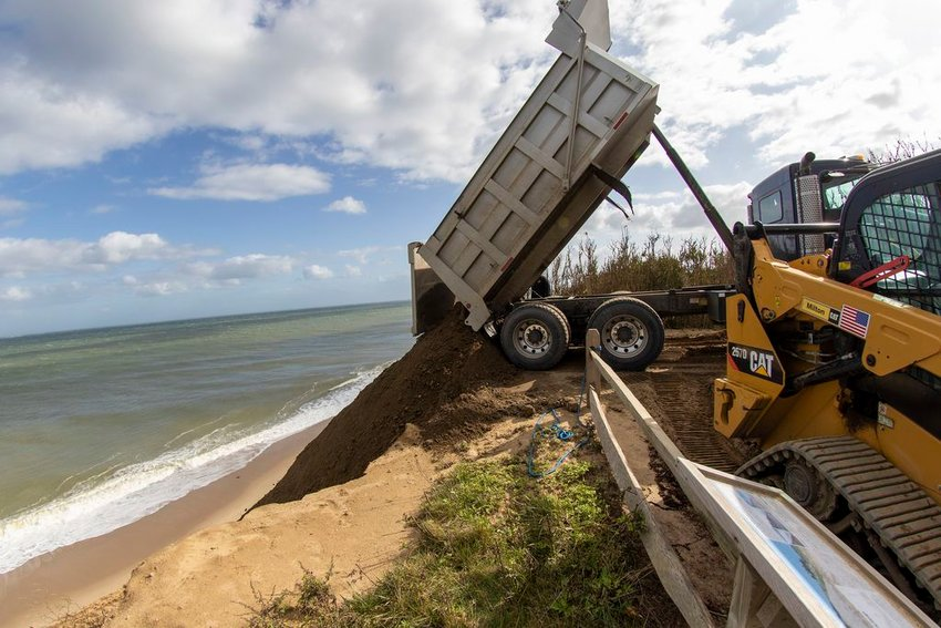 Contractors dump replenishment sand over the Sankaty  Bluff on to the Sconset Beach Preservation Fund's erosion-control project.