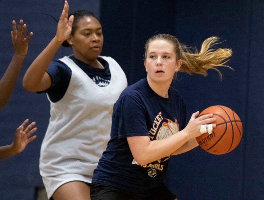Sydney King looks to pass as Madison Bird defends at girls basketball practice Friday.