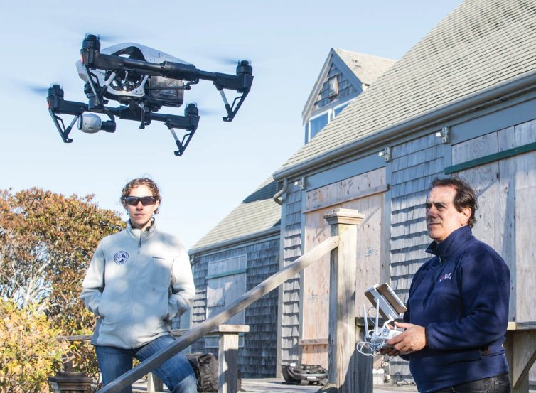 Nantucket Land Council resource ecologist Emily Molden looks on as Ron Fortunato launches a drone used to map the invasive species phragmites that borders Nantucket ponds.