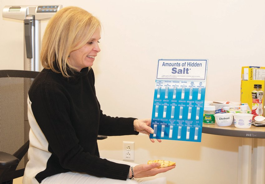 Photo by Nicole Harnishfeger.Suzanne Davis holding a chart showing the hidden salt found in common foods and sauces in her Nutrition and Wellness office at Nantucket Cottage Hospital.