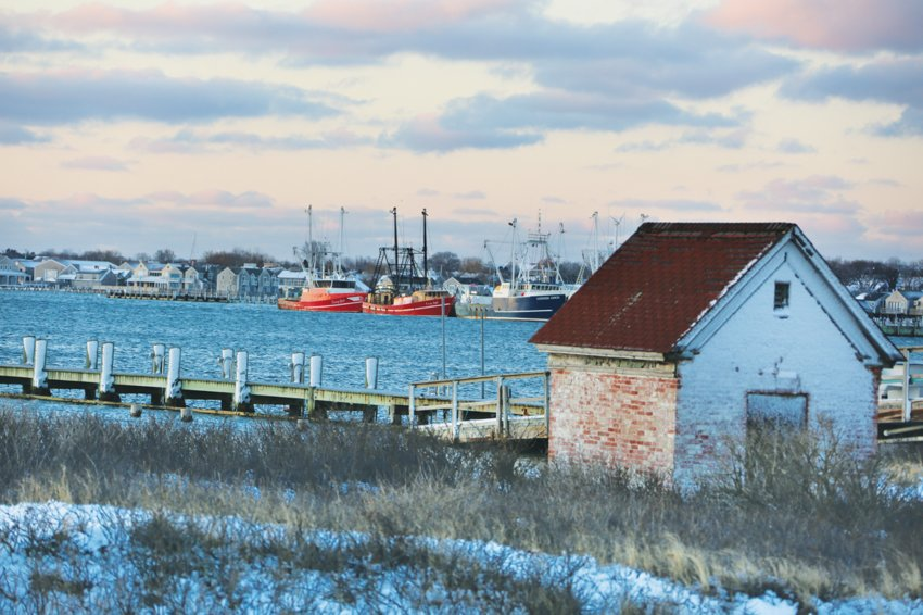 Fishing boats are tied up at the Nantucket Boat Basin Monday, as seen from a snowy Brant Point. Though it faces north, for fishing vessels at sea, Nantucket is often the closest port in a storm.